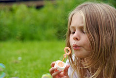 Girl blowing bubbles Stock Image