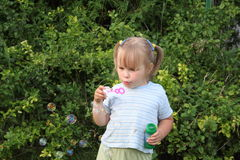 Girl blowing bubbles. Cute preschool girl blowing bubbles outdoors, trees in background Stock Photo