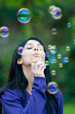 Girl blowing bubbles Stock Photos