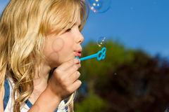Girl blowing bubbles. A little girl blowing bubbles in the garden Stock Photography