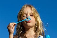 Girl blowing bubbles. A lovely young girl blowing bubbles against a vibrant blue sky Royalty Free Stock Image