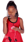 Girl blowing bubbles. Young African American girl blowing bubbles Stock Image