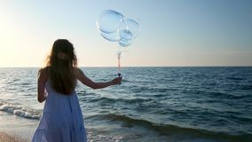 Girl blowing bubbles on beach in slow motion. A young girl blows soap bubbles in the evening, during sunset. Runs along stock video
