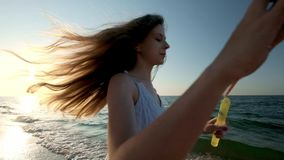 Girl blowing bubbles on beach in slow motion. A young girl blows soap bubbles in the evening, during sunset. Runs along stock video footage