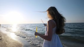 Girl blowing bubbles on beach in slow motion. A young girl blows soap bubbles in the evening, during sunset. Runs along stock footage