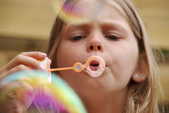 Girl blowing bubbles with bubble wand Stock Photo