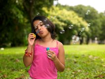 Girl blowing bubbles in the garden Royalty Free Stock Image