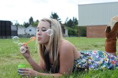 Girl Blowing Bubbles in Grass Stock Photo