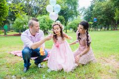 Girl blowing bubbles with her father and mother in park. Little girl blowing bubbles with her father and mother in park stock photography