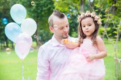 Girl blowing bubbles with her father in park. Little girl blowing bubbles with her father in park royalty free stock photos