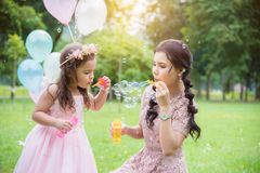 Girl blowing bubbles with her mother in park. Little girl blowing bubbles with her mother in park royalty free stock photo