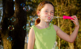 Girl Blowing Bubbles in Late Afternoon Royalty Free Stock Photography