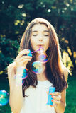 Girl blowing bubbles outdoors Royalty Free Stock Photos