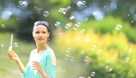 Girl blowing bubbles outdoors Stock Images