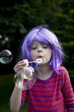 Girl blowing bubbles outdoors Stock Image