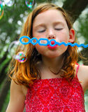 Girl blowing bubbles outside Royalty Free Stock Photography