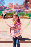 Girl blowing bubbles in the park Royalty Free Stock Photography