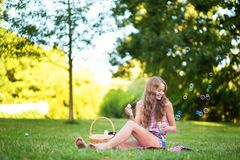 Girl blowing bubbles in park Royalty Free Stock Images