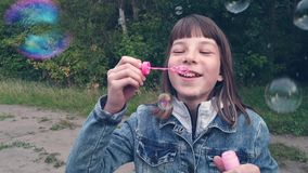 Girl blowing bubbles in the Park on a summer evening stock footage