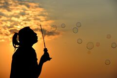 Girl blowing bubbles at sunset Royalty Free Stock Photo