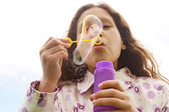 Girl blowing bubbles. Stock Images