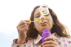 Girl blowing bubbles. Stock Photo
