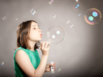 Girl blowing bubbles. Young girl blowing bubbles on a grey background Stock Photography