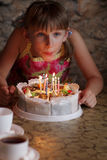 Girl is blowing on candle Royalty Free Stock Photos