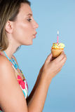 Girl Blowing Candle. Beautiful girl blowing birthday candle Royalty Free Stock Images