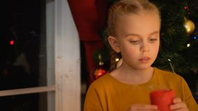 Girl blowing on candle, standing near window, waiting parents, Christmas eve. Stock footage stock video footage