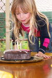 Girl blowing candles. A cute little girl blowing out candles on a birthday cake Stock Image