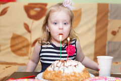 Girl blowing candles on birthday cake Stock Photography