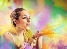 Girl blowing colored powders Royalty Free Stock Images