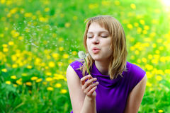 Girl is blowing on dandelion. Beautiful woman blowing dandelion on the meadow royalty free stock photos