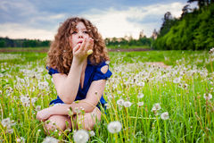 Girl blowing a dandelion Royalty Free Stock Photography