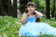 Girl blowing on dandelion. The little girl is sitting on the lawn in the park Royalty Free Stock Photography