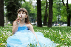 Girl blowing on dandelion. The little girl is sitting on the lawn in the park Royalty Free Stock Photo