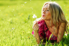 Girl blowing on a dandelion Stock Photo