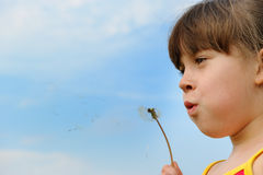 Girl blowing on a dandelion Royalty Free Stock Photography