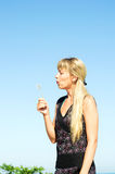 Girl blowing a dandelion. Young blond girl blowing a dandelion flower in ripened Royalty Free Stock Photo