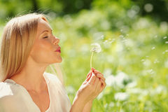 Girl blowing on a dandelion Stock Images