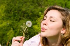 Girl blowing on the dandelion Royalty Free Stock Photography