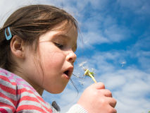Girl blowing a dandelion against a blue sky Stock Photo