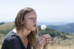 Girl blowing a dandelion in the field Stock Photo
