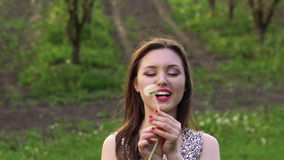 The girl blowing dandelion, looking aside and smiling . Slow motion.  stock footage