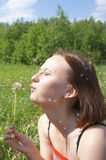 Girl blowing on dandelion Royalty Free Stock Photos