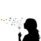 Girl blowing on dandelion. And the seeds are transforming into butterflies Stock Image