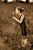 Girl blowing dandelion sepia tone. Little girl in dress and boots blowing dandelion wish Royalty Free Stock Images