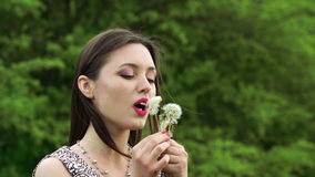 Girl blowing dandelion and smiling on a camera. Slow motion.  stock footage