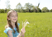 Girl blowing dandelions Stock Photos
